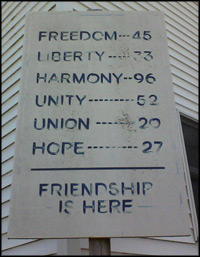 a sign on the corner of a building reading, Freedom-45, Liberty-33, Harmony-96, Unity-52, Union 26, Hope-27, Friendship is Here