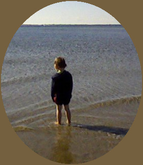 image of a young boy standing in shallow ocean water with small ripples, looking down into the water